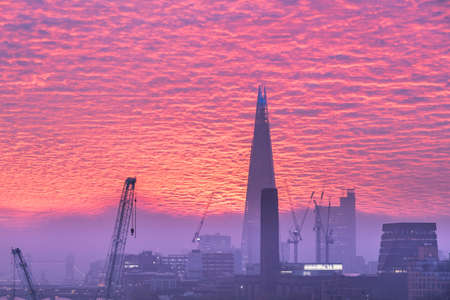 Epic sunrise over London city skyline with stunning sky formations over iconic landmarks Stock Photo