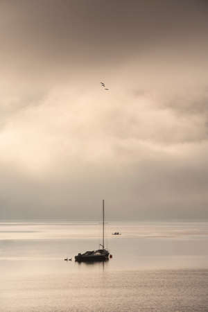 Beautiful calm image of sailing boat on Derwentwater in Lake District on a Winter morning