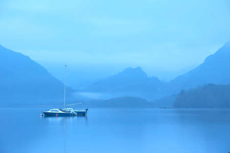 Beautiful landscape image of misty Derwentwater in Lake District on cold Winter morning