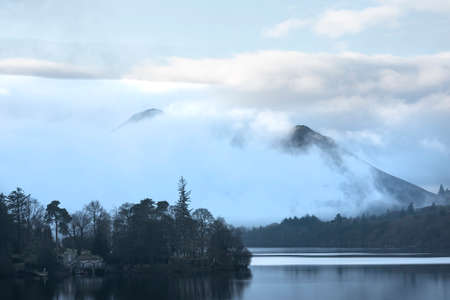 Epic landscape image looking across Derwentwater in Lake District towards Catbells snowcapped mountain with thick fog rolling through valley
