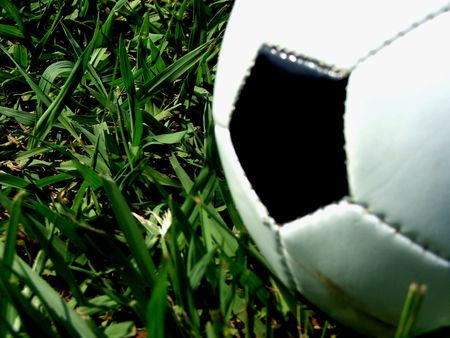 teammate: A close-up of a half Soccer ball over the grass Stock Photo
