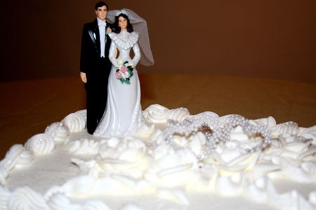 sugar veil: Close-up of a Wedding Cake with a wedding cake topper  over a gold table cloth