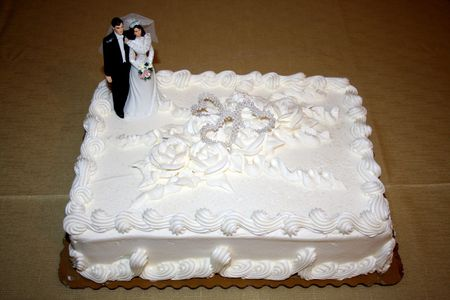 Wedding Cake with a wedding cake topper  over a gold table cloth photo