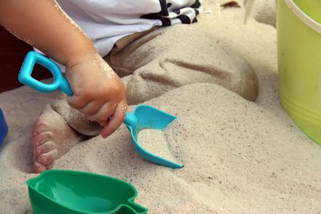 A kid playing in a Sand box