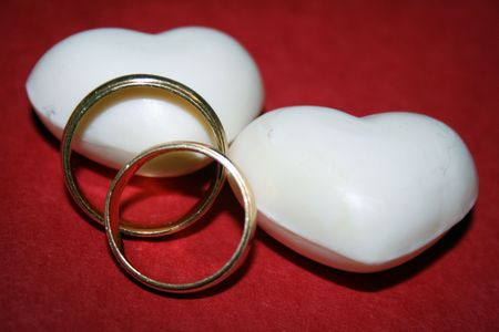 Two wedding rings with two white hearts over a red background Stock Photo - 4121594