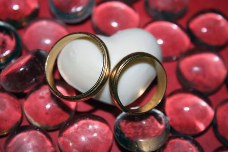 Two wedding rings over a white heart and glass pebbles