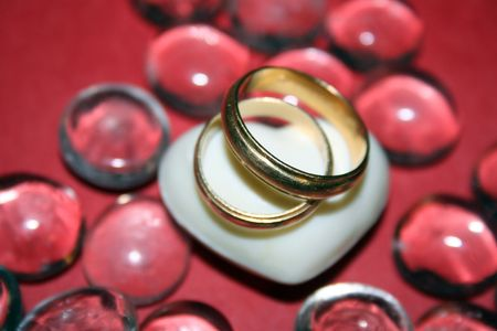 Wedding rings over a white heart and glass pebbles Stock Photo - 4121601