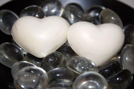 Two white hearts over glass pebbles in a black background Stock Photo