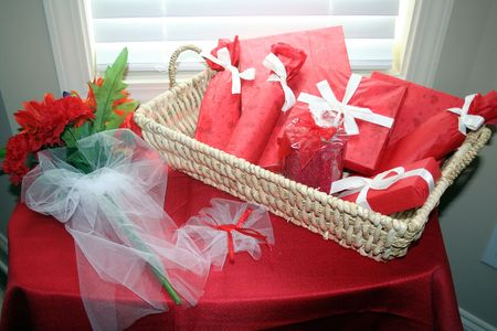 Basket fill with gift and a flower bouquet over a red tablecloth photo
