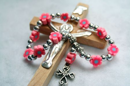 Close-up of a wood cross with a mini rosary