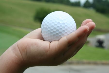 Kids hand holding a golf ball