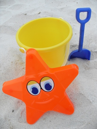 Star, bucket  and shovel in the sand photo