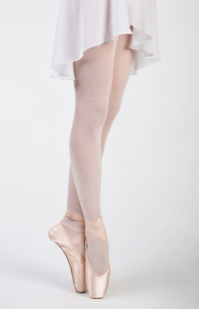 beautiful legs of a ballerina in pointe and light white skirt on white background photo