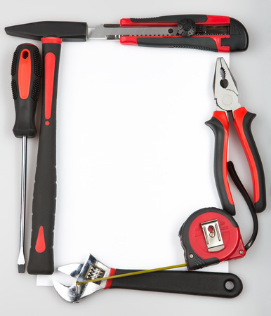 Tool set forming a frame on white background. Hammer, screwdriver, pliers, tape measure, cutting pliers, cutter, monkey wrench. Renovation project. photo
