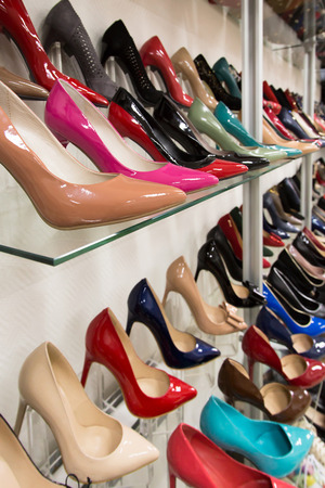 Rows of beautiful, elegant, colored womens shoes on store shelves. photo