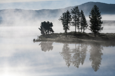 Morning mist over the lake. Island in a lake on a background of mountains photo