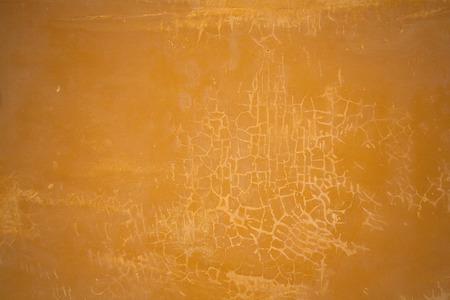 muur met gebarsten gips. abstracte achtergrond. textuur van oker kleur