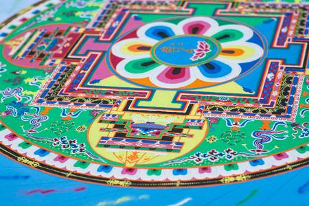 Creating a Buddhist green sand mandala blue floor.
