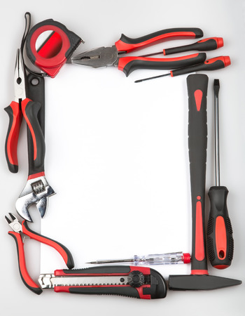 Tool set forming a frame on white background. Hammer, screwdriver, pliers, tape measure, cutting pliers, cutter, monkey wrench. Renovation project. Stock Photo