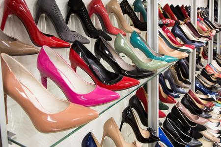 Rijen van mooie, elegante, gekleurde schoenen van vrouwen in de winkelrekken. Stockfoto