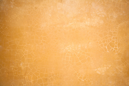 ocher: wall with cracked plaster. abstract background. texture of ocher color