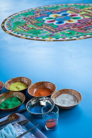 tantra: Creating a Buddhist green sand mandala blue floor.