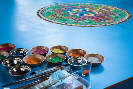 moine: Création d'un mandala de sable vert sol bleu bouddhiste.