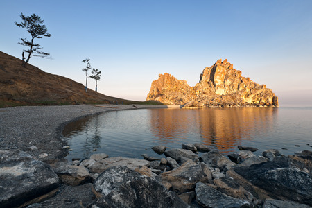 Golden rock on the shore of the lake at dawn. Lake Baikal. photo
