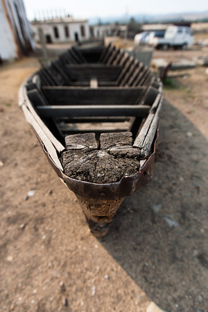 shallop: Old collapsed wooden boat close up on a sandy beach.