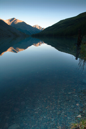 Clear water of a mountain lake at sunset. Mountains lit by the setting sun and reflected in the lake photo