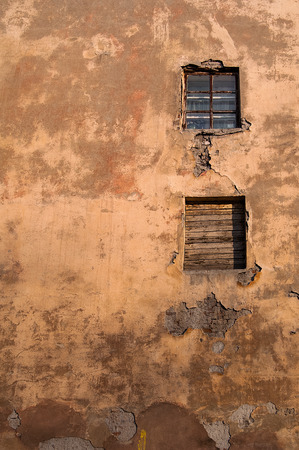 Two window on the old wall with cracked plaster. photo