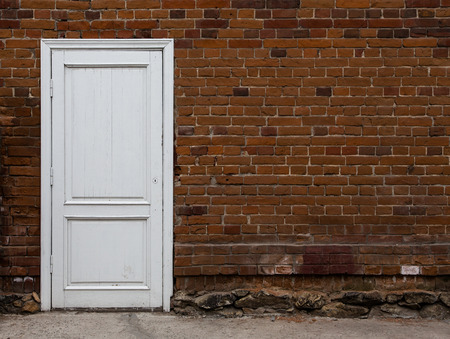 White wooden door on an old brick wall. Abstract background with brick wall and door. photo