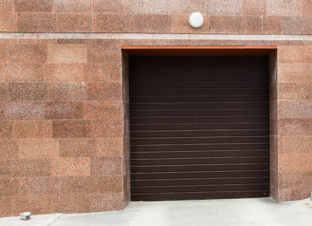 Entrance to the garage, block storage, with sliding doors red marble wall. photo
