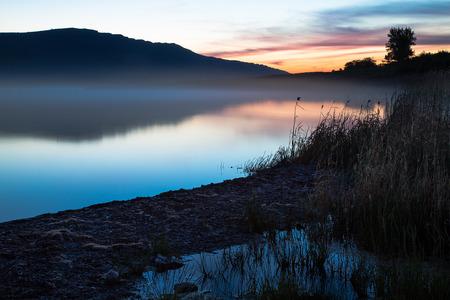 Dawn op het meer Harmony, kalme water van het bergmeer nacht