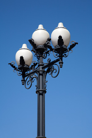 Street cast iron antique lamp with three white with glass plafonds on a background of blue sky