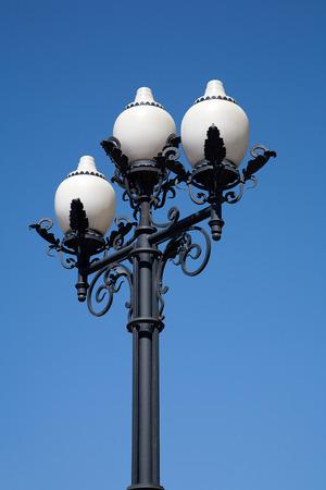 Straat gietijzeren antieke lamp met drie witte met glazen plafonds op een achtergrond van blauwe hemel Stockfoto - 37178493
