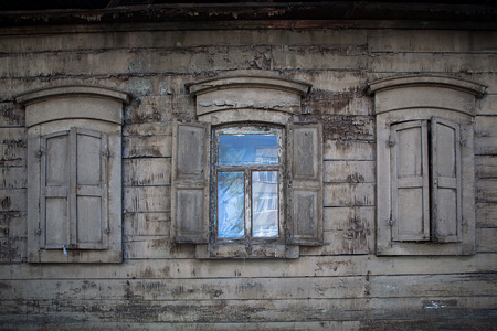 Three old wooden windows with wooden shutters. Open window in rural house.