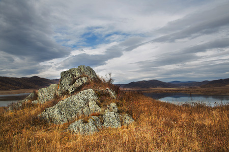 Autumn, stone, rock in the grass in the hills on background blue sky