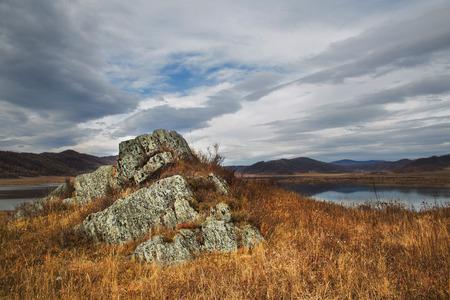 Herfst, steen, rots in het gras in de heuvels op de achtergrond blauwe hemel