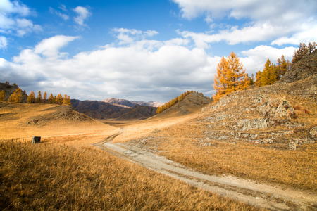 Autumn, ground road stretches into the distance among hills and rocks on background blue sky Stockfoto