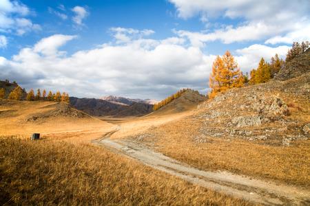 De herfst, grond weg strekt zich uit in de verte tussen de heuvels en de rotsen op de achtergrond blauwe hemel