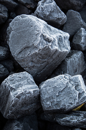 Close up of chunks black coal on which the is visible rime. Morning snow on the rocks of coal Stockfoto