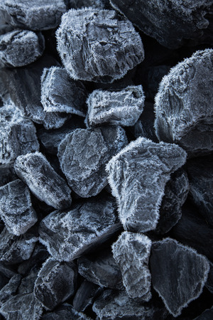 Close up of chunks black coal on which the is visible rime. Morning snow on the rocks of coal photo