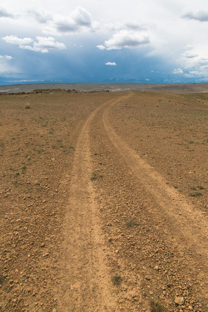 dirt road running along the steppe hills and leaving to the horizon Stockfoto