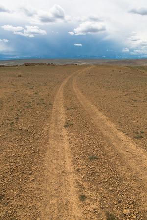 onverharde weg loopt langs de steppe heuvels en het verlaten van de horizon