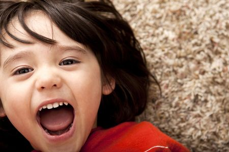 biracial: A cute, bi-racial toddler boy is surprised and laughing. Stock Photo