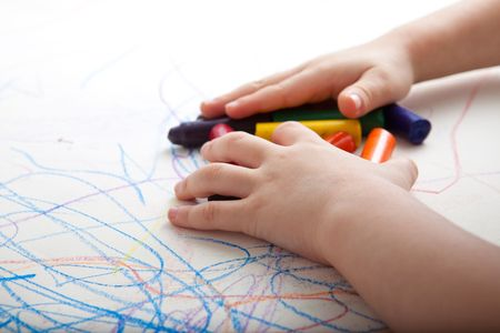 games hand: Child is gathering up colors on top of creative drawings.