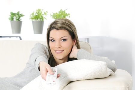young woman in her sofa activating a remote control TV Stock Photo - 8942875