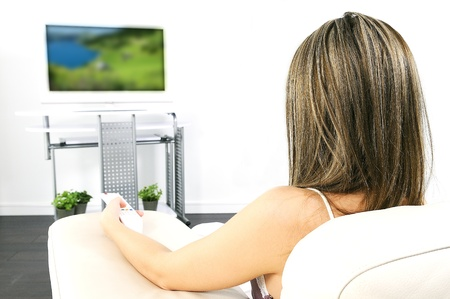 woman watching tv: Woman in living room watching television