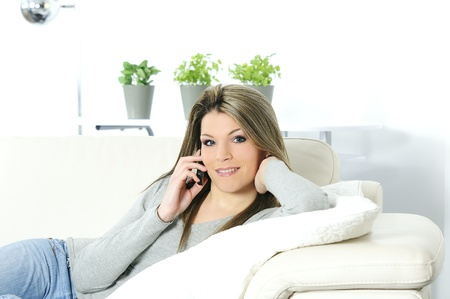 young beautiful woman on telephone in his sofa photo
